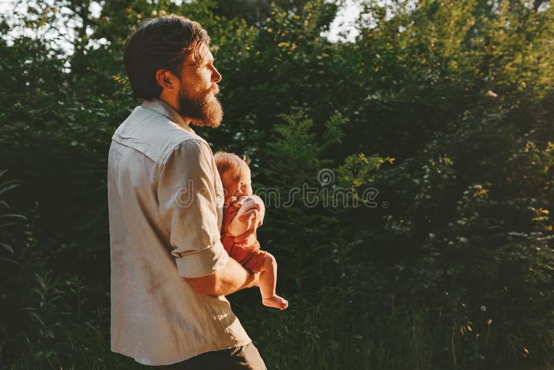 Father holding infant baby walking together in forest royalty free stock photo
