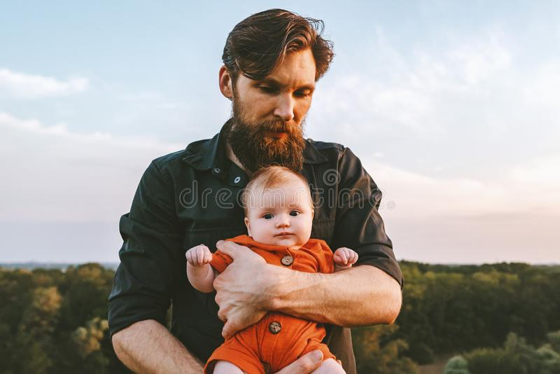 Father holding infant baby walking together outdoor royalty free stock image