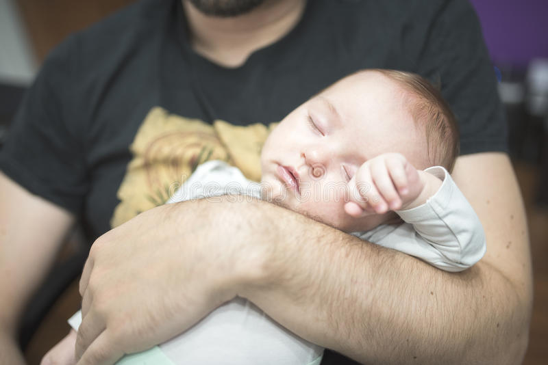 Father holding sleeping child stock images