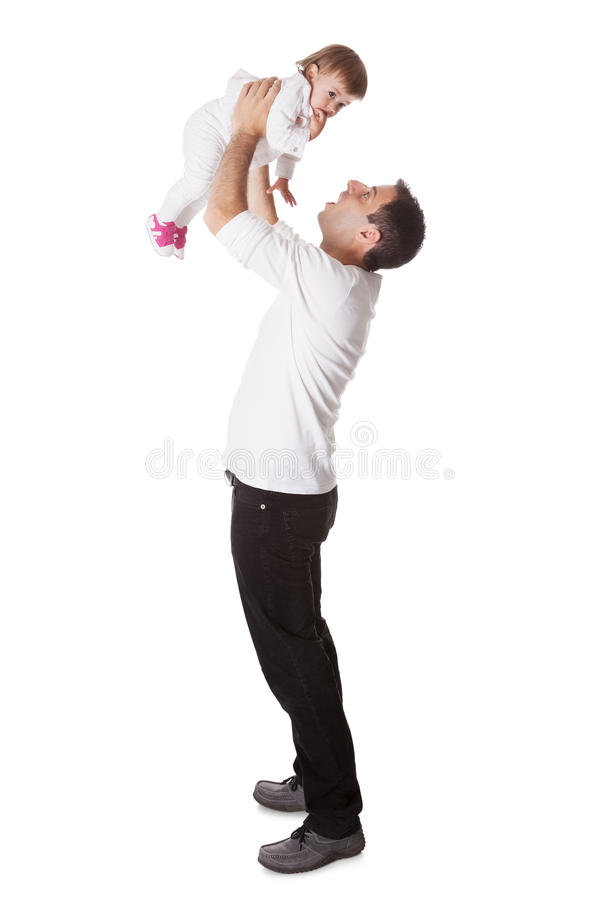 Father holding small baby aloft. Young father playing with his small baby daughter holding her aloft with his arms extended above his head stock image