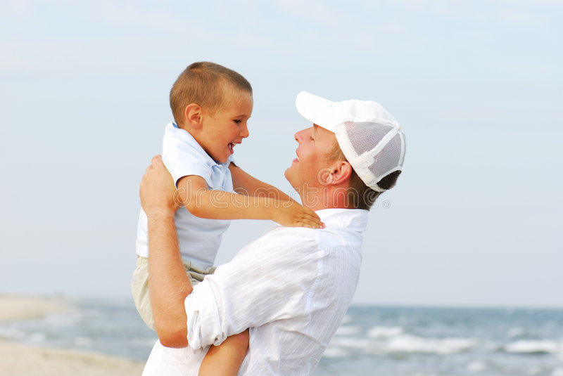Father holding son by sea stock images