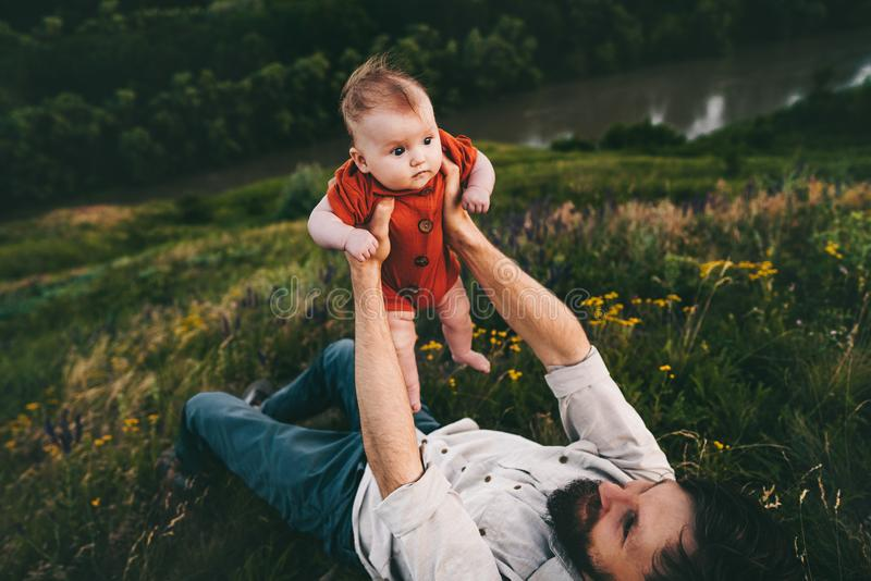 Father holding up baby lying on grass outdoor happy family royalty free stock photography
