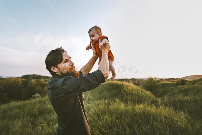 Father holding up baby playing together outdoor stock photos