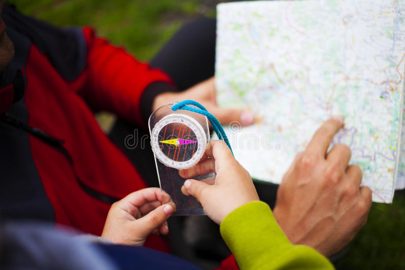 Father holds the card, a child holding a compass. royalty free stock photo