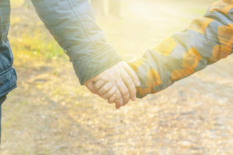 The father holds his son`s hand. Hands of a boy and a man together close-up, in the light of the rays of the sun.  Concept of fam royalty free stock photo