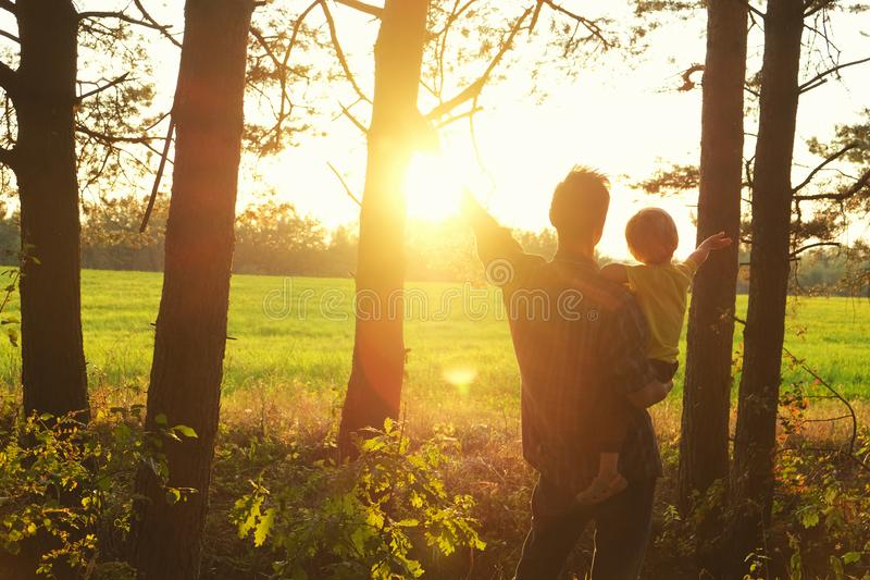 Father holds his toddler son in his arms and they open hands togerher to meet beautiful sunset on the edge of forest. Father`s da royalty free stock image