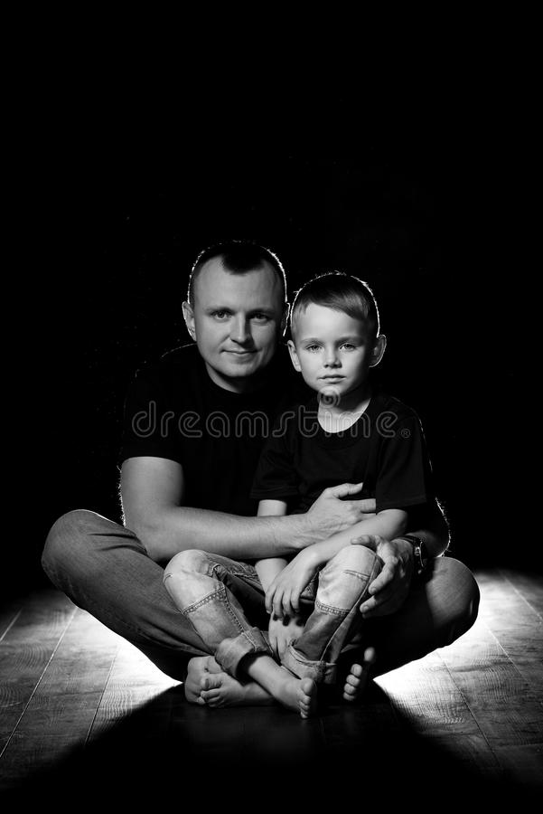 Father holds son in his arms and hugs him. Man and boy are sitting together against a black background. Happy fatherhood and royalty free stock image