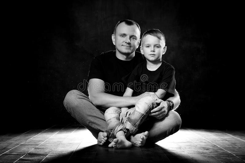 Father holds son in his arms and hugs him. Man and boy are sitting together against a black background. Happy fatherhood and royalty free stock photo