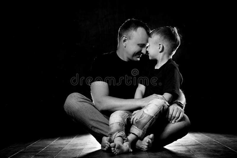 Father holds son in his arms and hugs him. Man and boy are sitting together against a black background. Happy fatherhood and stock images