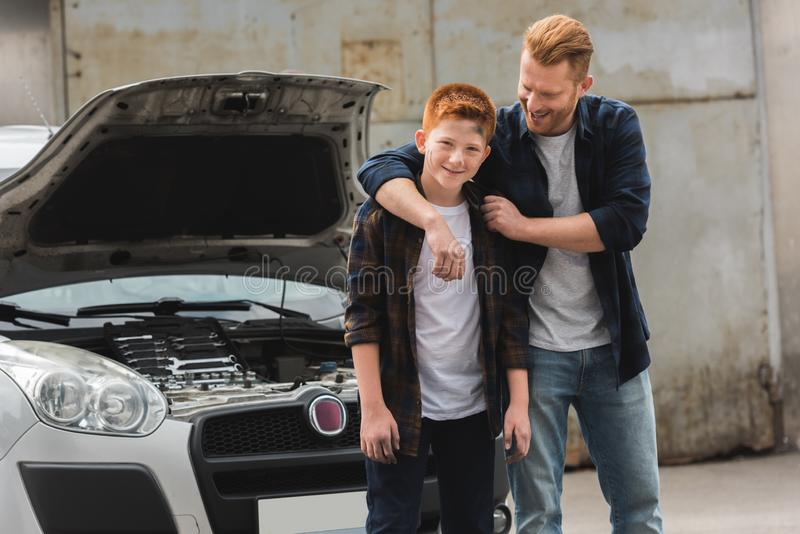 Father hugging son after repairing car. With open hood stock photography