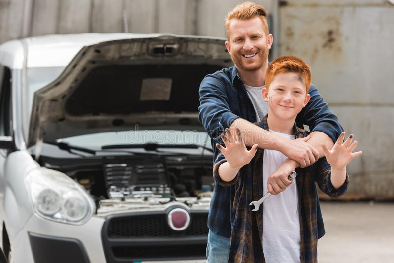 Father hugging son after repairing car and he. Waving hand royalty free stock photography