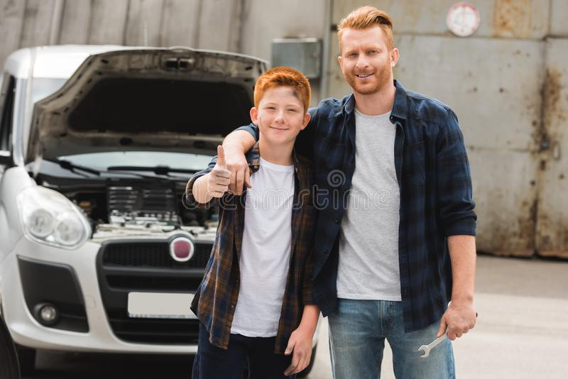 Father hugging son after repairing car and he showing. Thumb up stock images