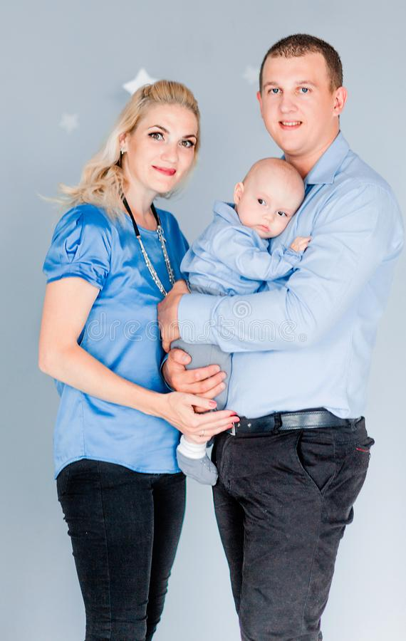 Father hugs his wife and son. Happy family looking at camera. Photo of Father hugs his wife and son. Happy family looking at camera stock images