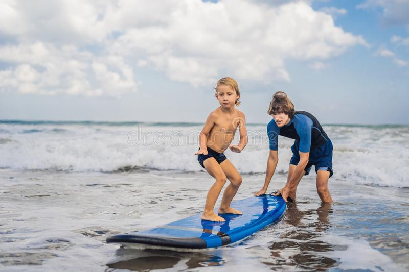 Father or instructor teaching his 4 year old son how to surf in stock images