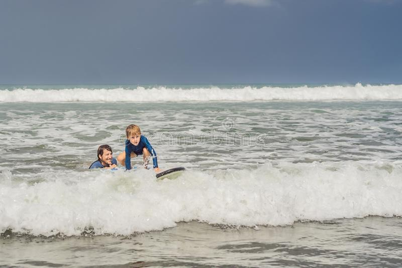 Father or instructor teaching his 5 year old son how to surf in the sea on vacation or holiday. Travel and sports with stock photo