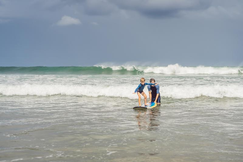 Father or instructor teaching his 5 year old son how to surf in the sea on vacation or holiday. Travel and sports with royalty free stock photos
