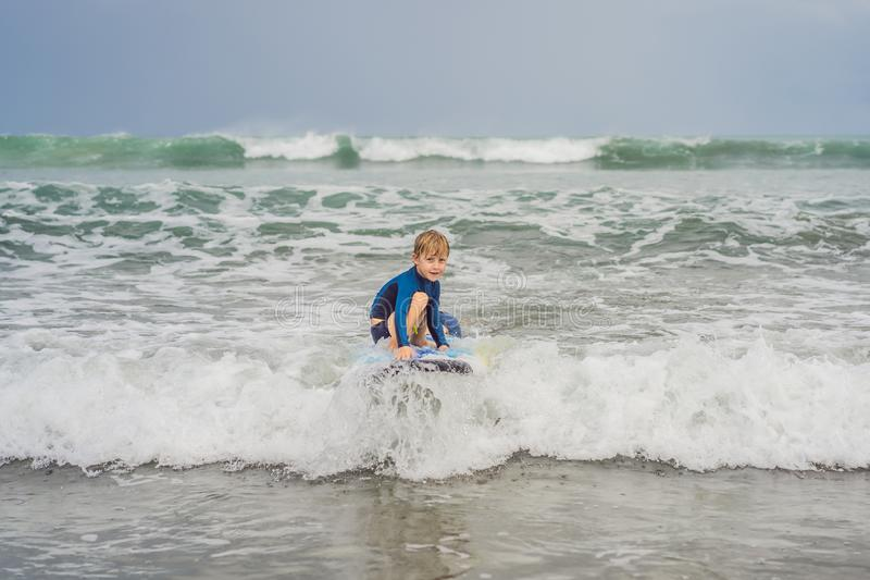 Father or instructor teaching his 5 year old son how to surf in the sea on vacation or holiday. Travel and sports with royalty free stock photography