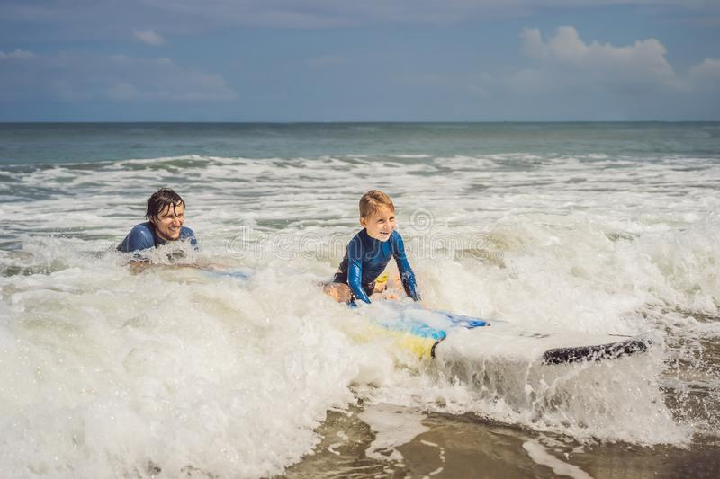 Father or instructor teaching his 5 year old son how to surf in the sea on vacation or holiday. Travel and sports with stock image