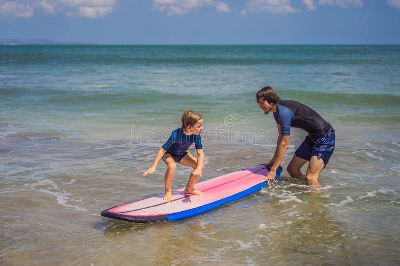 Father or instructor teaching his 5 year old son how to surf in the sea on vacation or holiday. Travel and sports with. Children concept. Surfing lesson for royalty free stock photography