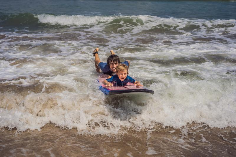 Father or instructor teaching his 5 year old son how to surf in the sea on vacation or holiday. Travel and sports with stock photography