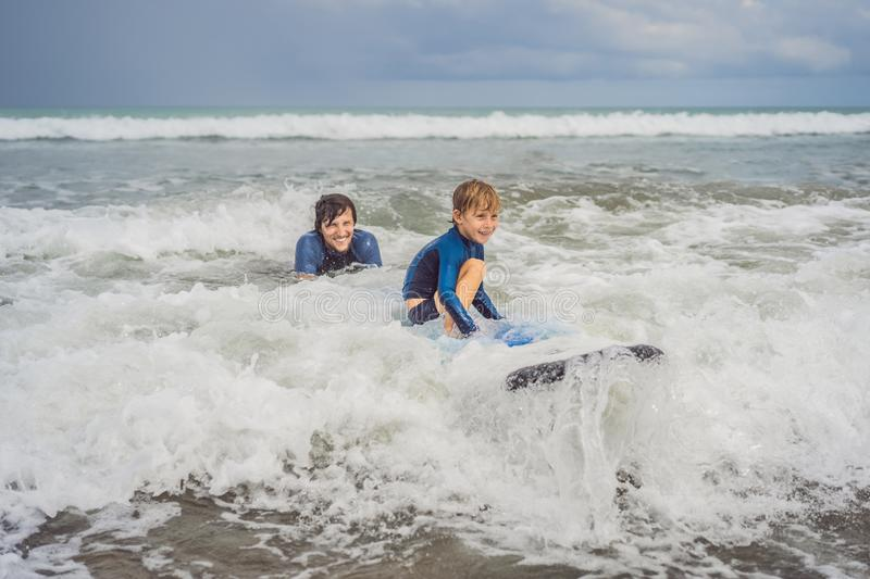 Father or instructor teaching his 5 year old son how to surf in the sea on vacation or holiday. Travel and sports with stock photos