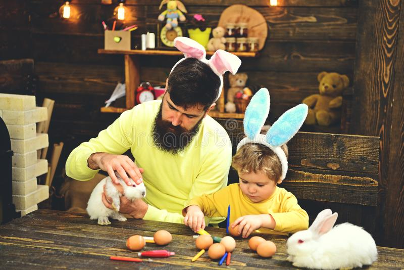 Father and kid painting Easter eggs. royalty free stock photo