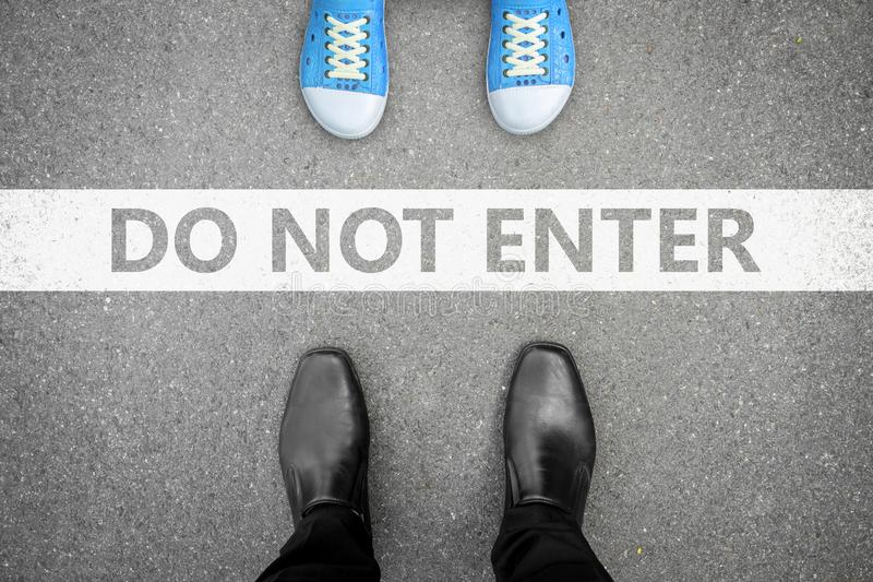 Father and kid in problem. Father in black shoes standing opposite kid in blue shoes . Between them is a line saying do no enter. They are in family problem stock photos