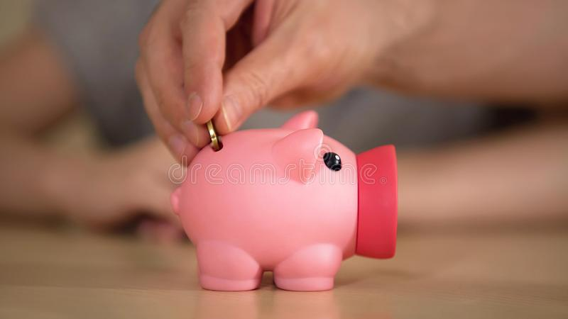 Father and kid putting money in piggy bank for purchase, saving family budget stock image