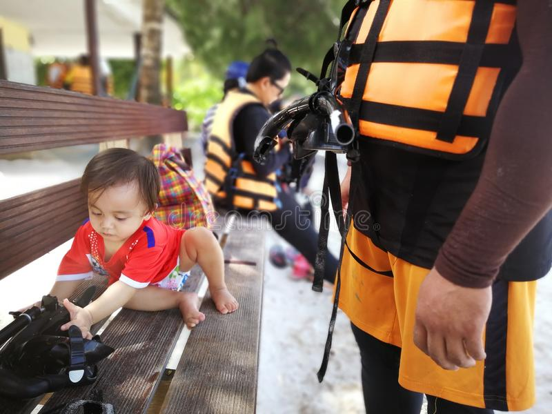 Father and kid waiting for a speedboat trip in a tropical island. Father wearing a life jacket stock photos