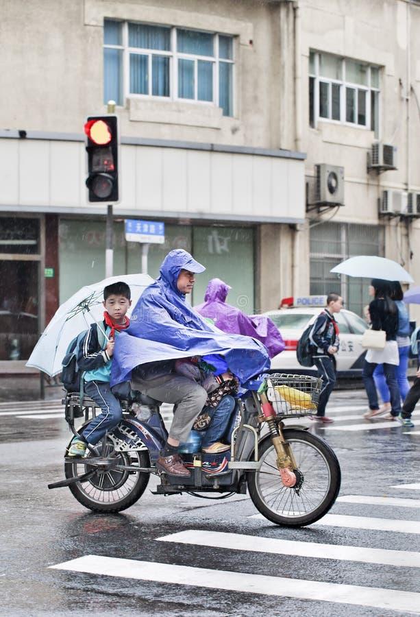 Father and kids dressed in rainwear on an e-bike, Shanghai, China stock photos