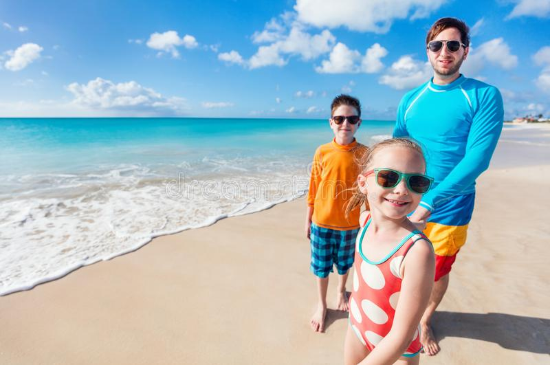 Father with kids at beach. Father and kids enjoying Caribbean beach vacation on tropical island royalty free stock photography