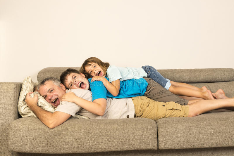 Father and kids playing on the sofa royalty free stock photo