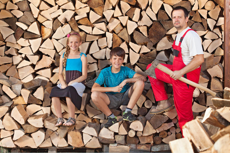 Father and kids prepared to chop firewood and stack it into a wood shed stock photos