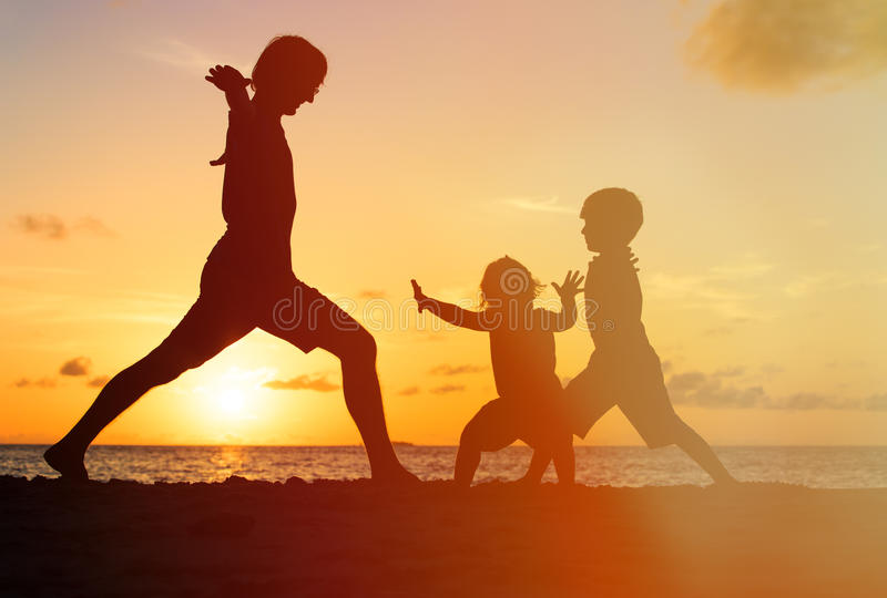 Father with kids silhouettes having fun at sunset royalty free stock photography