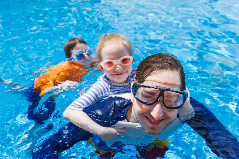 Father and kids at swimming pool stock images