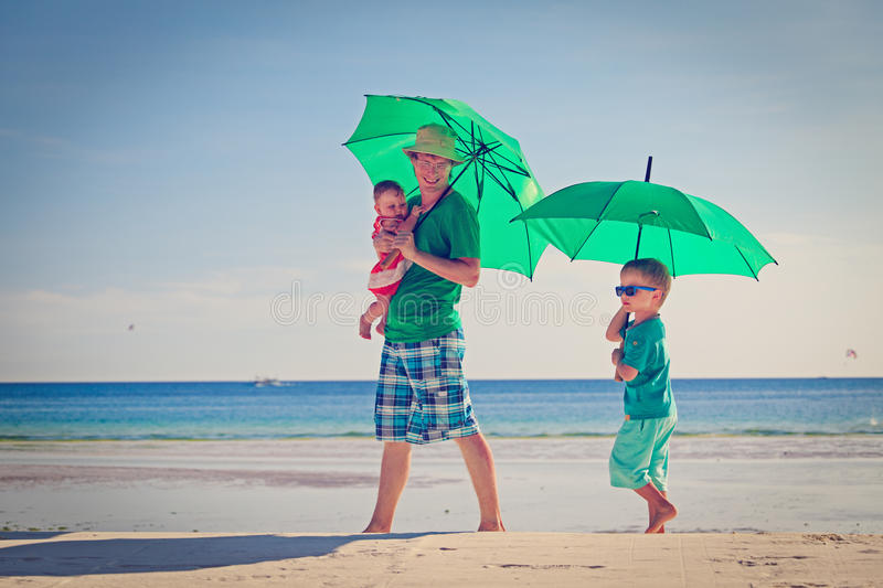 Father and kids with umbrellas on beach vacation stock photos
