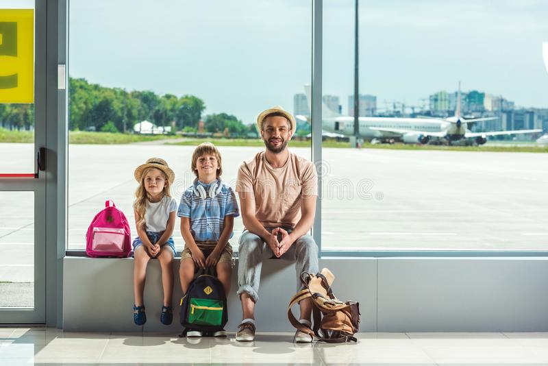 Father and kids waiting for boarding stock images