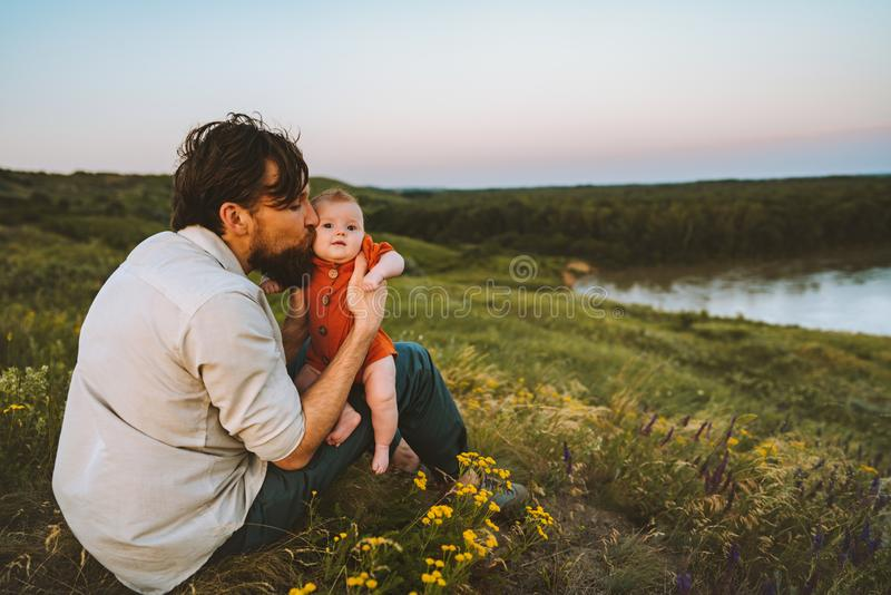Father kissing baby daughter walking outdoors happy family stock photo