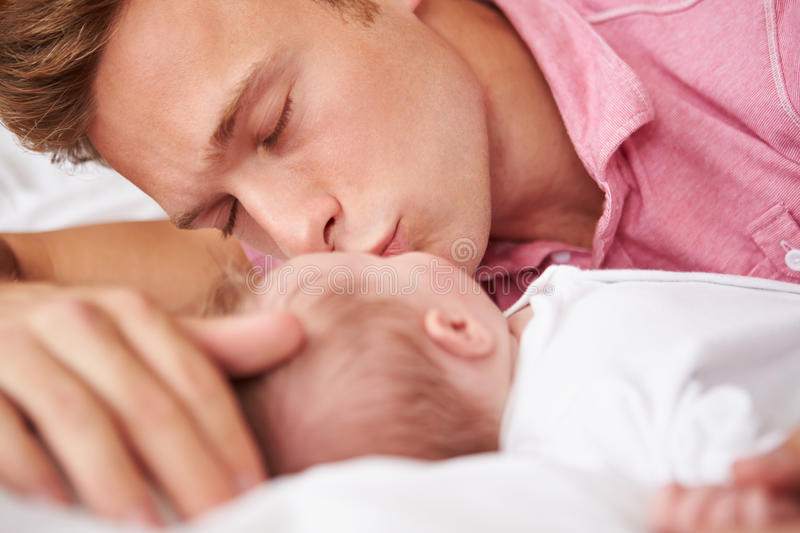 Father Kissing Baby Girl As They Lie In Bed Together royalty free stock photography