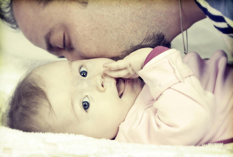 Father kissing his little baby girl. Young father kissing his little blue eyed baby girl royalty free stock photo