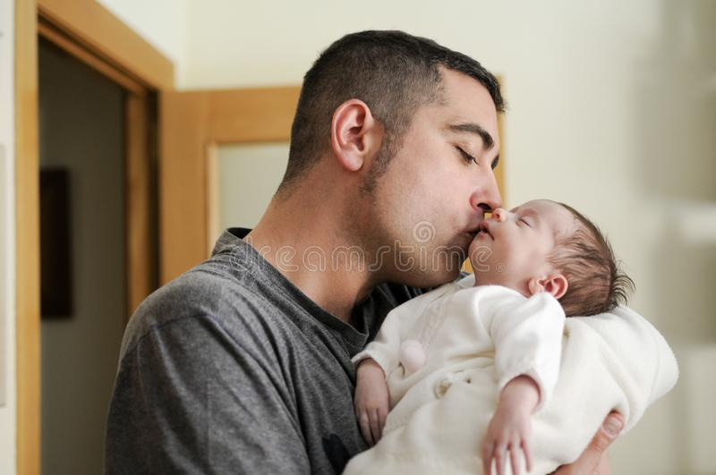 Father kissing his newborn baby girl royalty free stock photos