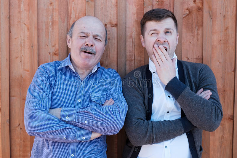 The father-in-law and son-in-law standing by the wooden wall. stock photos
