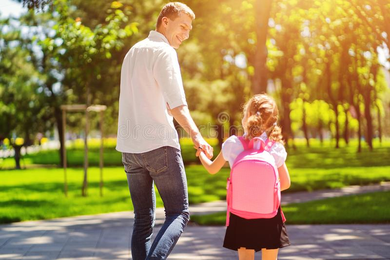 Father leads daughter to school in first grade. first day at school. back to school royalty free stock photography
