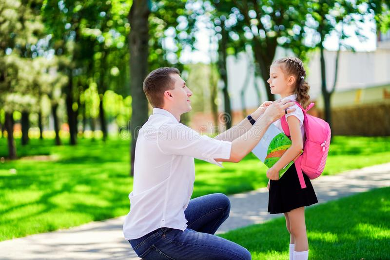 Father leads daughter to school in first grade. first day at school. back to school royalty free stock image