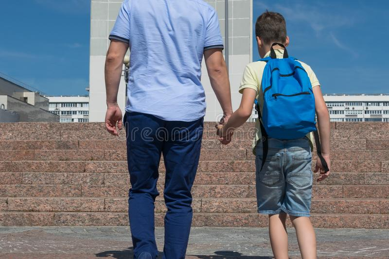 Father leads his son up the stairs to school, close-up stock photography