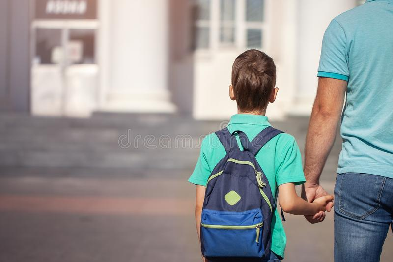 Father leads a little child school boy go hand in hand. Parent and son with backpack behind the back royalty free stock photography