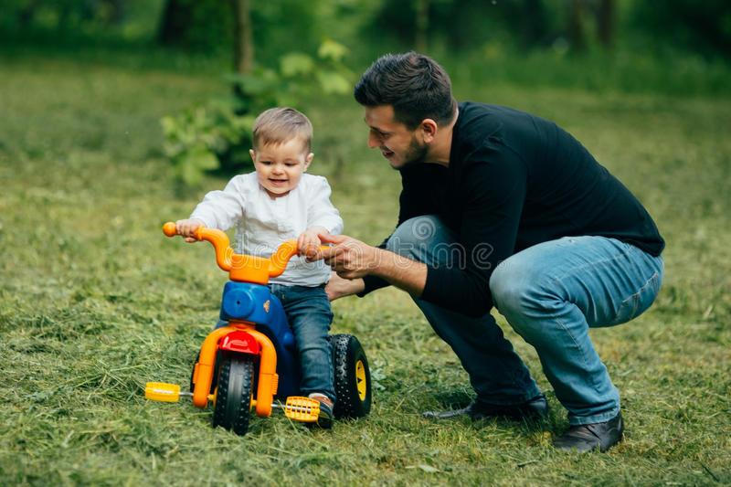 Father learn kid to ride a small bicycle royalty free stock image
