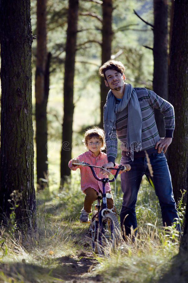 Download Father Learning His Son To Ride On Bicycle Outside Royalty Free Stock Image - Image: 33787716