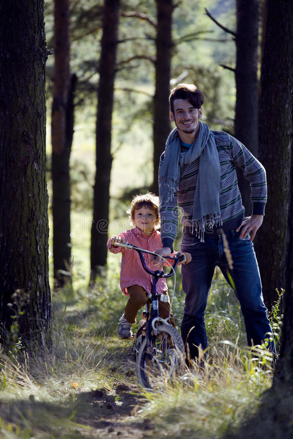 Download Father Learning His Son To Ride On Bicycle Outside Stock Photo - Image: 33787722