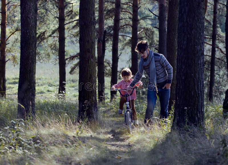 Download Father Learning His Son To Ride On Bicycle Outside Royalty Free Stock Photo - Image: 33787725